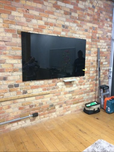 black magnetic glassboard mounted on brick city office wall